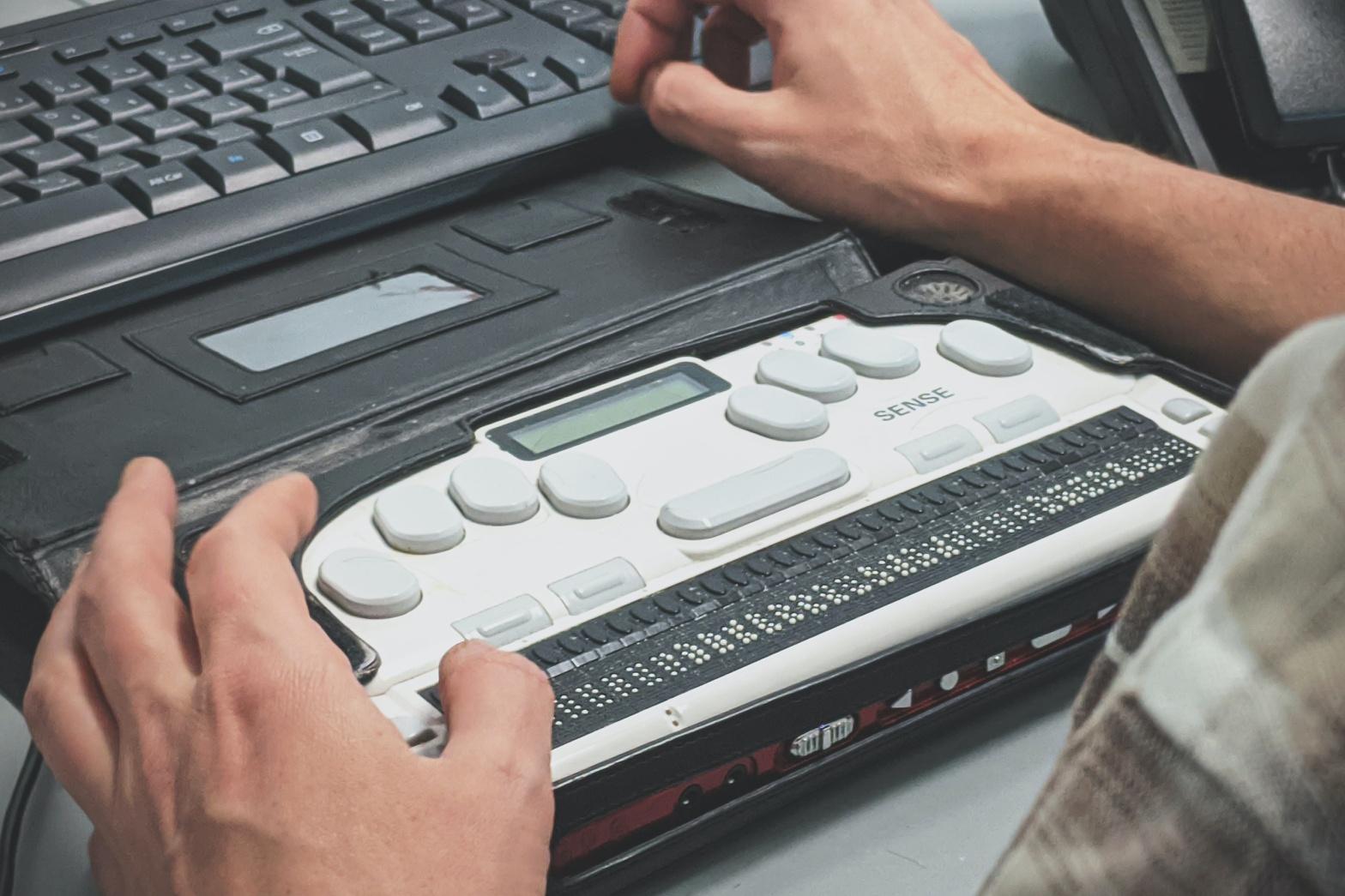 Hands using a braille machine